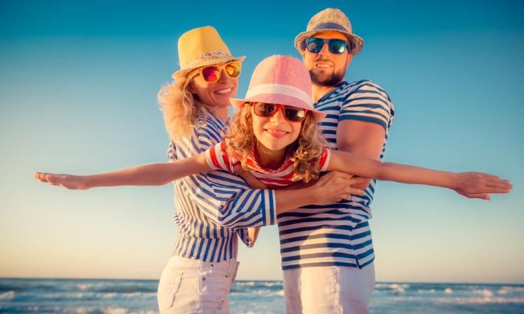 Couple at the beach wearing striped blue shirts holding their daughter in a red striped shirt, with hats and sunglasses