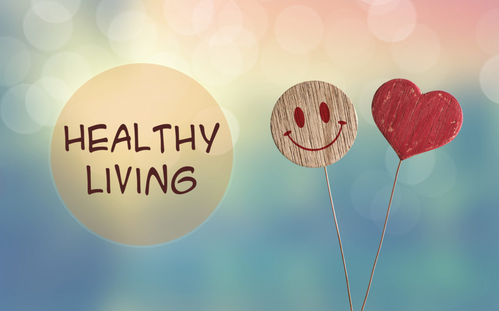 A bubble with the words Healthy Living next to a smiley face and heart balloons against a whimsical background