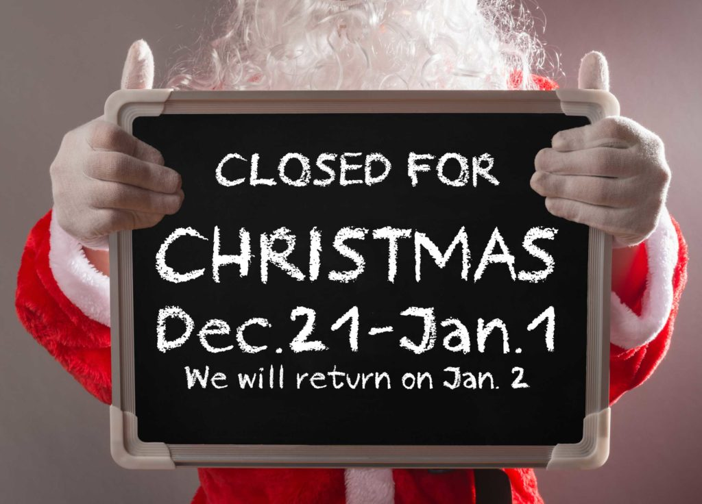 Santa holding a chalkboard informing patients Michael Gillespie Family Dentistry is closed December 21-January 1